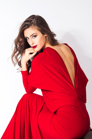 lean back: young elegant woman in red dress sit on chair studio shot Stock Photo