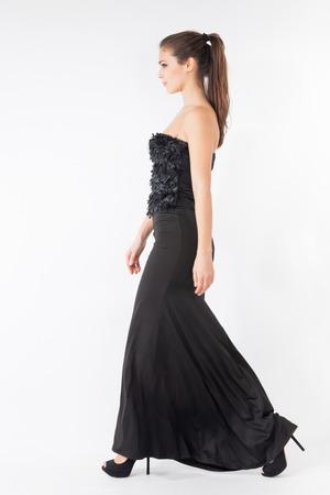full body shot: mujer que camina en la larga elegante foto de estudio negro vestido de cuerpo completo