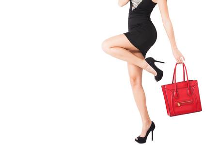 corps de la femme en robe noire courte, chaussures à talons hauts tenir dans la main handbeg rouge