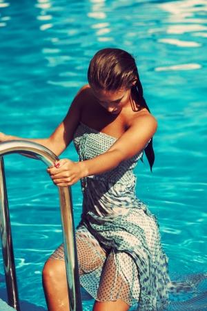 umida: donna di uscire dalla piscina indossa il vestito blu