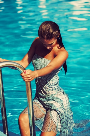 woman get out from the pool wearing blue dress Stock Photo