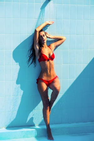 sexy shower: sexy woman in red bikini under shower on pool hot summer day Stock Photo