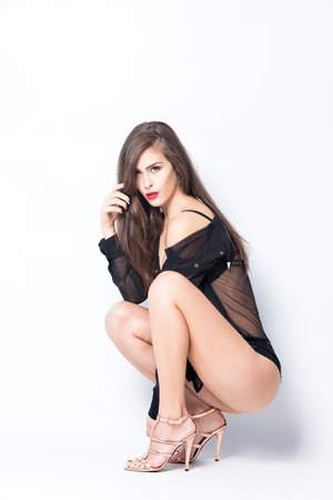 long legs: sexy woman in black lingerie,  transparent shirt  and high heel shoes full body shot, studio
