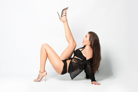 lingerie model: sexy woman in black lingerie,  transparent shirt  and high heel shoes full body shot, studio