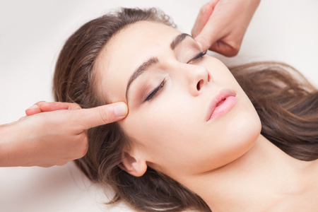 acupressure hands: woman acupressure face massage closeup Stock Photo