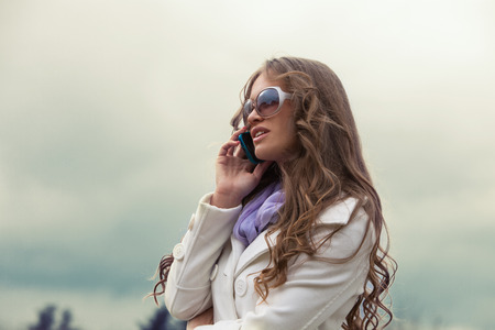 white coat: elegant young woman in white coat and sunglasses  talking on smartphone outdoor shot