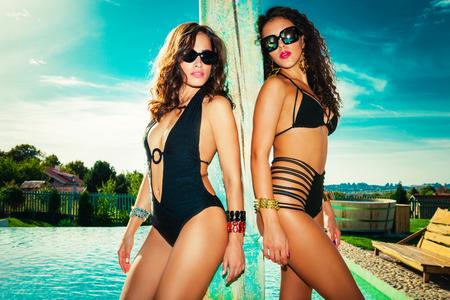 paar junge Frauen in Badekleidung am Pool Sommer heißer Tag Standard-Bild