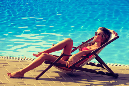 sunbath: woman relax  by the pool take sunbath sunny summer day