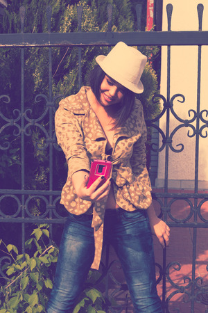 instagram: young woman take a picture of herself with smartphone, selfie, retro colors