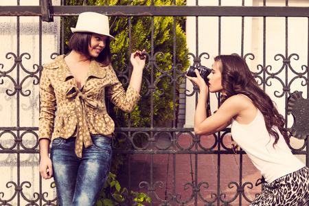 avocation: woman photographer take a photo of young woman with camera outdoor shot