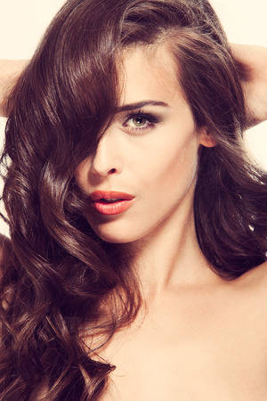 hair studio: beautiful young woman with long wavy brown hair studio shot