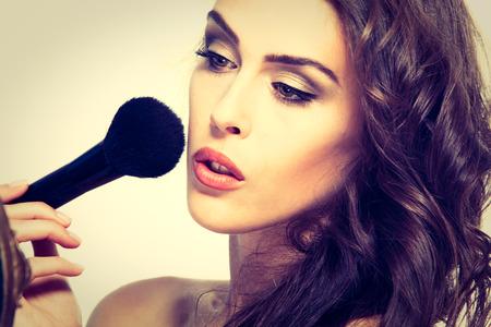 beautiful young woman apply makeup studio shot photo