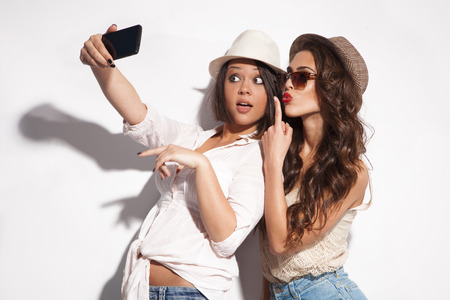 two young women taking selfie with mobile phone  Stock Photo