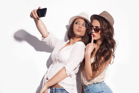 携帯電話で selfie を取る 2 人の若い女性