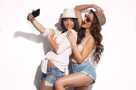 photographing: two young women taking selfie with mobile phone  Stock Photo