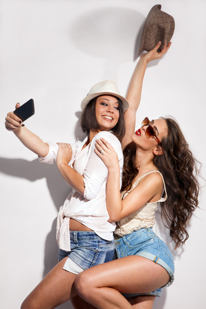 taking photograph: two young women taking picture of them selfs with mobile Stock Photo