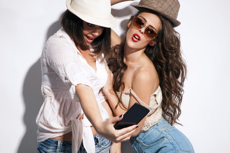 two young women taking picture of them selfs with mobile photo