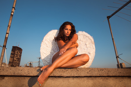 naked woman sitting: angel woman on building roof, summer day, Belgrade, Serbia