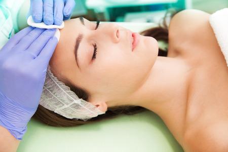 pulizia viso: donna al trattamento di cosmetici viso Archivio Fotografico