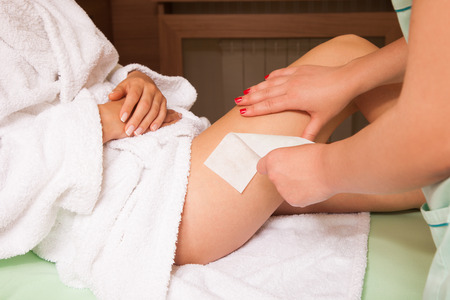 waxing: woman at cosmetics salon waxing legs