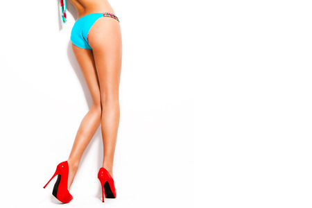 woman in blue bikini and red high heel shoes studio white background photo