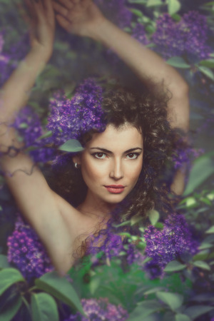 fantasy forest fairy surrounded by flowers Stock Photo