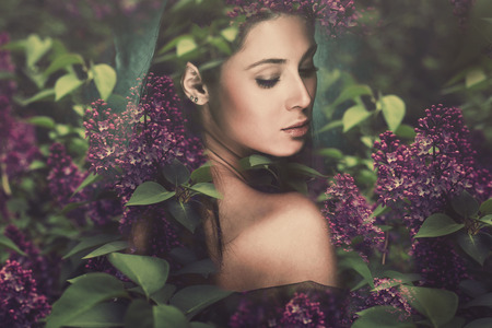 fantasy forest fairy surrounded by flowers photo