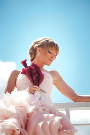 blonde bride in elegant wedding-dress hold flower bouquet lean on fence outdoor summer day photo
