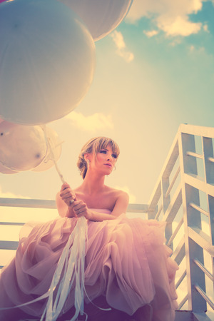 young beautiful woman in elegant wedding dress hold balloons sitting on  white stairs against sky with clouds, retro colors photo