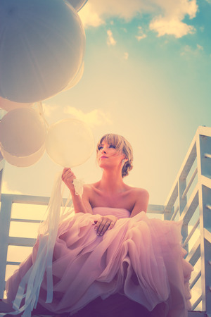 young beautiful woman in elegant wedding dress hold balloons sitting on  white stairs against sky with clouds, retro colors Standard-Bild