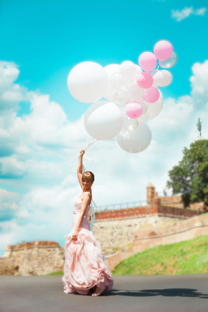 エレガントなウェディング ドレスで幸せな花嫁の保持の風船屋外夏の日、フルボディ ショット、バック グラウンドでベオグラードの要塞