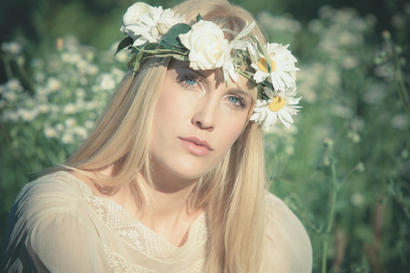blue eyes blonde young woman summer portrait with wreath of flowers photo