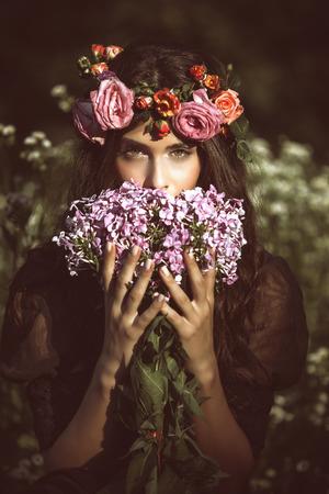 フィールドの夏の日のレトロな色の花を持つ若い美しい女性の肖像画