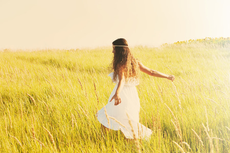 happy smiling woman in boho style clothes run  through the field, sunny summer day, retro colors Stock Photo