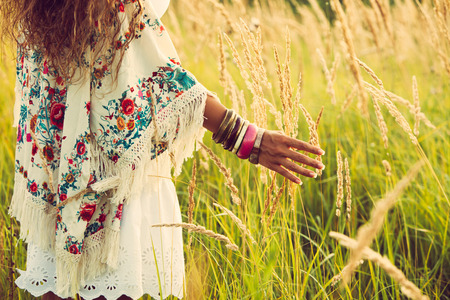 woman wearing boho style clothes touching grass, hand with lot of braceletes, summer day in the field, retro colors photo