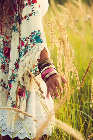 chic woman: woman wearing boho style clothes touching grass, hand with lot of braceletes, summer day in the field, retro colors