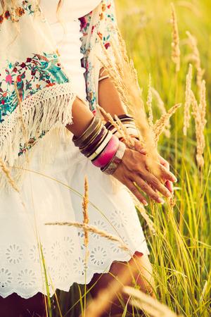 Frau Boho-Stil Kleidung berühren Gras, von Hand mit viel braceletes, Sommertag im Feld, Retro-Farben Lizenzfreie Bilder - 30148350