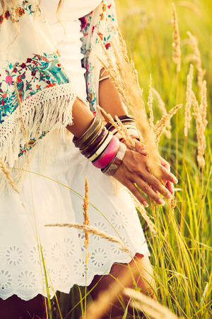 woman wearing boho style clothes touching grass, hand with lot of braceletes, summer day in the field, retro colors