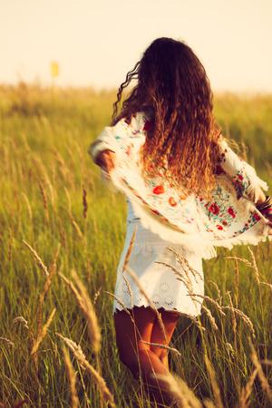 hot summer: mujer vestida con ropa de estilo boho correr por la hierba, caluroso d�a de verano, colores retro, el desenfoque de movimiento