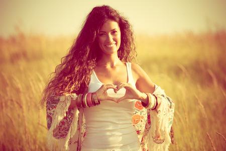 lachende jonge vrouw in de zomer veld show hart vorm hand teken
