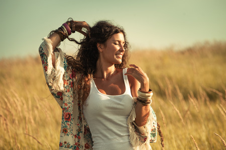 smiling young  woman wearing boho style clothes enjoy in summer day on the field of grass, retro colors