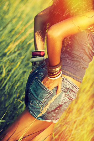 hot legs: young woman in jeans shorts wearing lot of braceletes on hand standing in yellow summer grass side shot retro colors