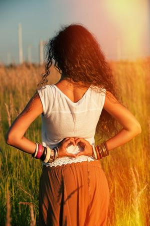 detras de: joven vuelve un disparo en el campo de verano con las manos corazón shape