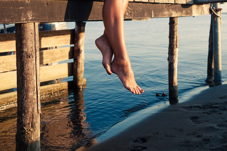 woman legs as she sitting on old wooden dock at sea shore