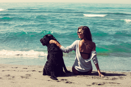 young woman and her dog sit by the water on sandy sea beach