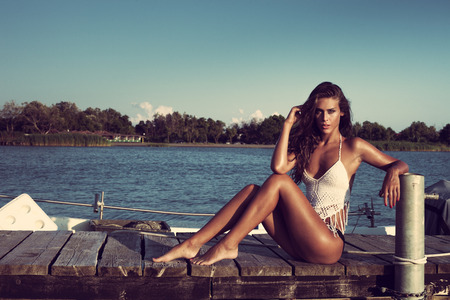 attractive tanned young woman relaxing on wooden dock on sea, full body shot
