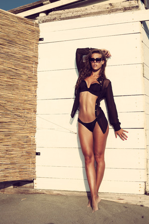 attractive young woman in black bikini and shirt posing on white wood wall on beach full body shot Stock fotó