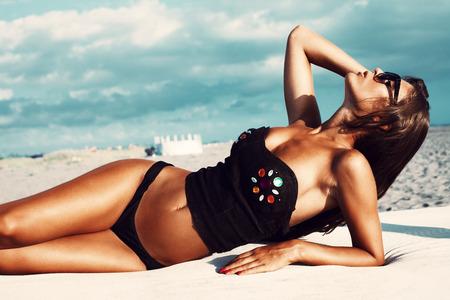 sunbath: attractive young woman with sunglasses in bikini and black top lie and take sunbath on beach