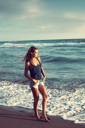 young woman in blue jeans shorts walk on sandy beach by the sea photo
