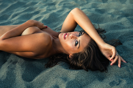 sensual young woman lie in sand at sunset Stock Photo